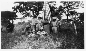 Former President Theodore Roosevelt (1858-1919) and other members of his expedition party from the Smithsonian Roosevelt African Expedition stand next to an American flag. Roosevelt is standing to the left of the flag with his head to the side. Other men in the image include Kermit Roosevelt, Edgar Alexander Mearns, and John Alden Loring. On this trip, Roosevelt collected natural history specimens for the United States National Museum (now National Museum of Natural History) and live animals for the National Zoological Park